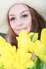 Smiling girl with yellow tulips over green background