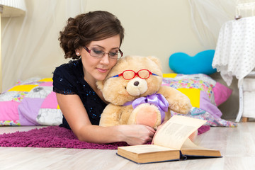 Serious girl and teddy bear reading a book in glasses