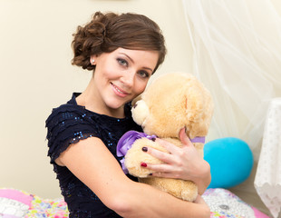 Smiling young woman with teddy bear