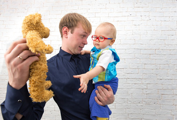 Young dad shows teddy bear to his one year old son on brick back