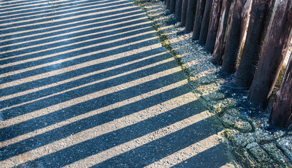 Parallel shadows of a row of wooden poles