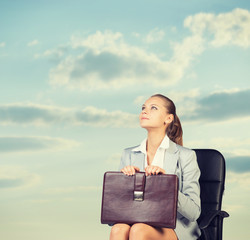 Business woman in skirt, blouse and jacket, sitting on chair