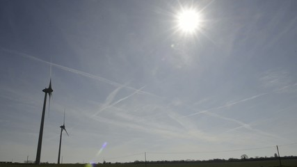 wind turbine on a blue sky with a few clouds