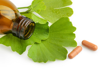 Ginkgo biloba leaves and medicine bottles with pills isolated