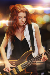 red haired woman playing guitar on stage