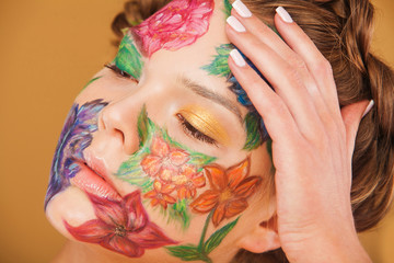 Close up portrait of woman model with hand drawing flowers on