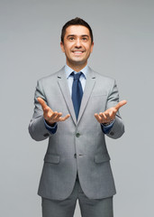 happy businessman in suit showing empty palms