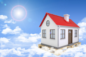 White house with red roof and chimney  in clouds. Background sun
