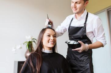 happy young woman coloring hair at salon