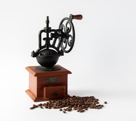 Vintage manual coffee mill with roasted coffee beans isolated