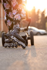 Woman Rollerblading While Pushing Baby Stroller