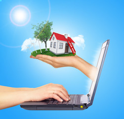 White shack in hand with red roof and chimney of screen laptop