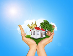 Hands holding house on green grass with crown, red roof, chimney