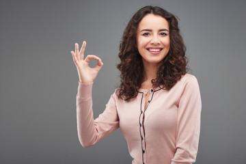 Young woman smiling and showing ok sign