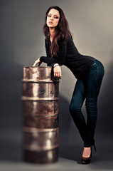 girl in jeans standing near the iron barrel