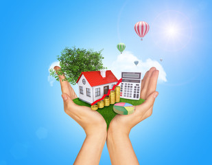Hands holding green grass with house on ground. Standing tree