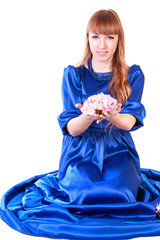 Young attractive woman sitting in a long blue evening dress