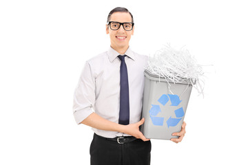 Young man holding a recycle bin full of shredded paper