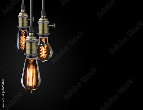 Old glowing light bulbs on black background