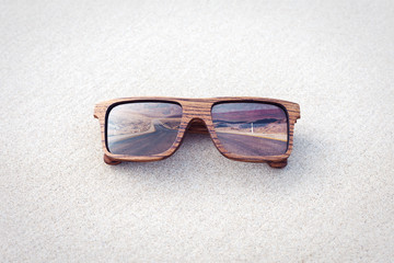 double exposure of wooden sunglasses  and desert road