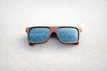 double exposure of wooden sunglasses and blue ocean