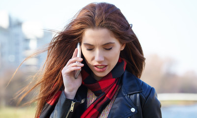 Portrait of pretty girl outdoor, talking on a cell phone