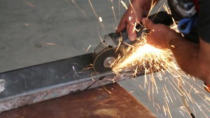 Industrial factory worker using grinder to cut metal