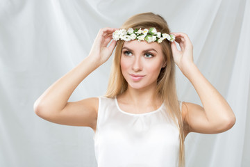 blonde girl, with a wreath of spring flowers,