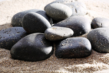 Pile of sea pebbles on shiny sand background