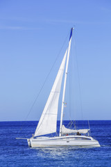 Yacht sailing in open azure sea
