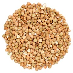 Raw wholegrain green buckwheat in round shape, isolated