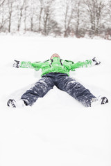 Young boy lying stretched out in the snow