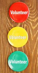 Round volunteer buttons on wooden background