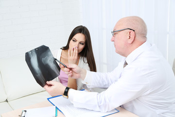 Doctor receiving X-ray results in office on white background