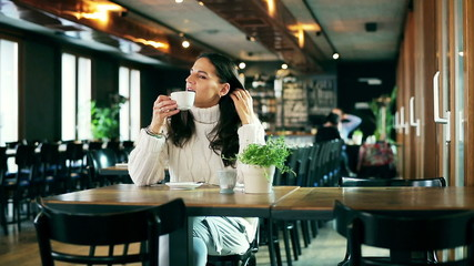 Happy woman drinking coffee in the restaurant and relaxing