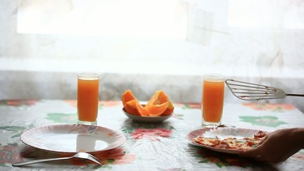 waitress lays eggs in a plate on the table. Breakfast with juice