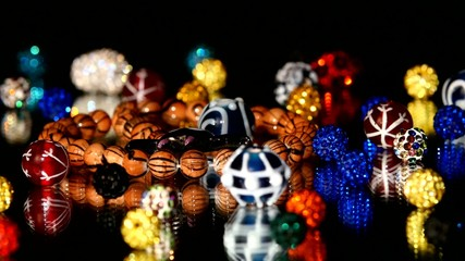 Different colorful beads on black background, cam moves to the