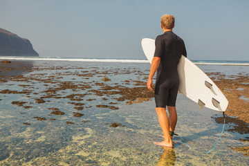 Surfer with surfboard on a coastline