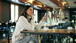 Happy woman sitting in the restaurant and chatting on smartphone