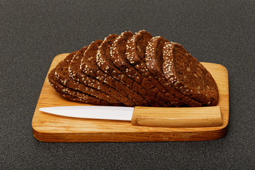 grain brown bread, sliced on the wooden plate
