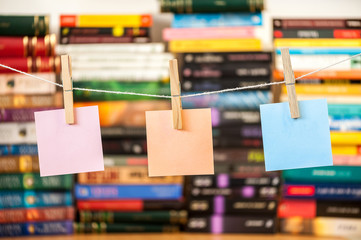 clear post it on string with pegs with books blurred background