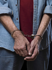 Close up of the arms of a mature man with handcuffs