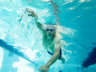 senior man swimming laps, underwater view