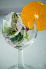 A glass with frosted leaves and orange