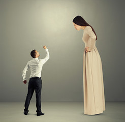 man showing fist to dissatisfied woman