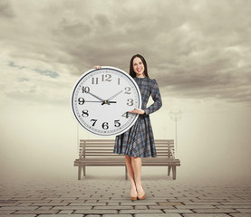 woman holding big clock and pointing