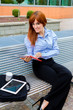 Businesswoman sitting outside on a metal bench while smiling