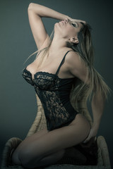 Blonde woman with black lingerie posing on a chair
