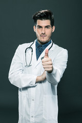 Doctor making positive thumb gesture over grey background