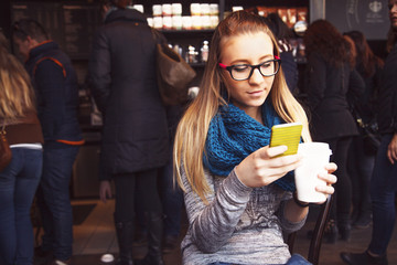 Girl sitting in cafe, texting message and drinking coffee.